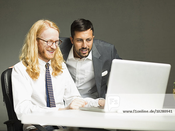 Businessmen looking at laptop in office