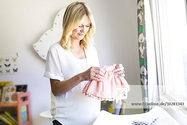 Frau halten Kleidung Schwangerschaft Baby