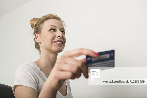 Receptionist holding a insurance card and smiling  Munich  Bavaria  Germany