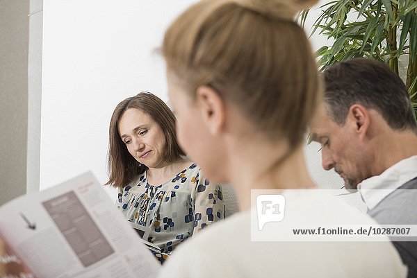 Three people sitting in waiting area of hospital  Munich  Bavaria  Germany