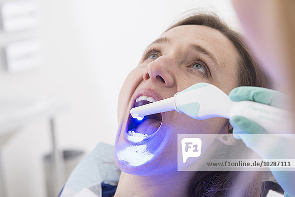 Woman receiving dental filling drying procedure  Munich  Bavaria  Germany