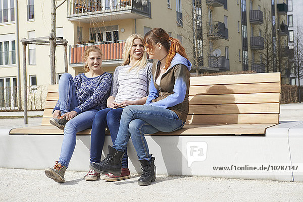 Three friends sitting on a bench in a playground  Munich  Bavaria  Germany