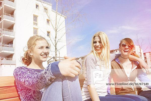 Three friends sitting on a bench in a playground  Munich  Bavaria  Germany