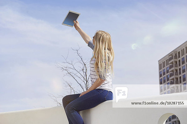 Teenage girl sitting on a wall and taking selfie with digital tablet  Munich  Bavaria  German