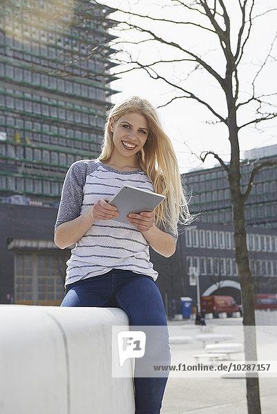 Teenage girl using a digital tablet in a playground  Munich  Bavaria  Germany