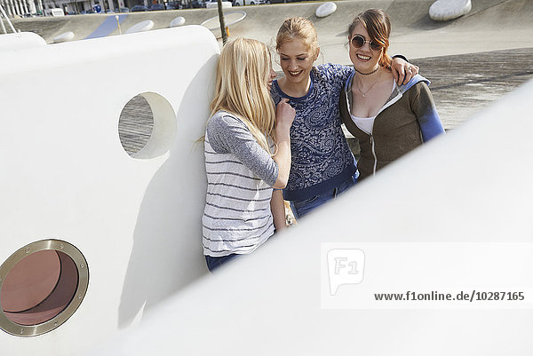 Three friends smiling in a playground  Munich  Bavaria  Germany