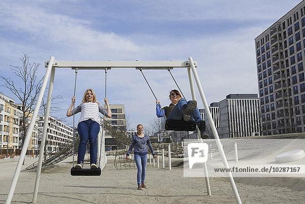 Friends swinging in a playground  Munich  Bavaria  Germany
