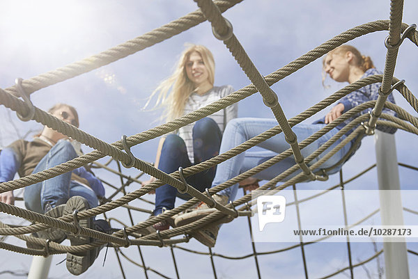Three friends sitting on climbing net in playground  Munich  Bavaria  Germany