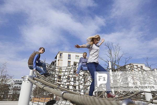 Three friends playing on climbing net in playground  Munich  Bavaria  Germany