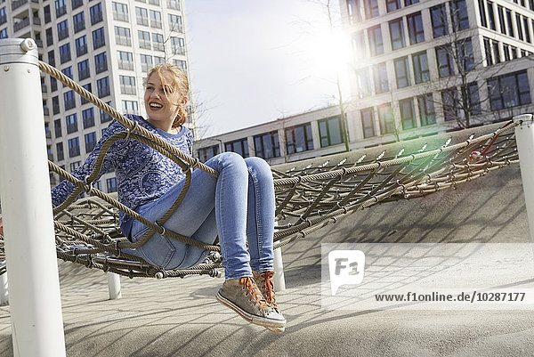 Young woman sitting on a climbing net in playground  Munich  Bavaria  Germany