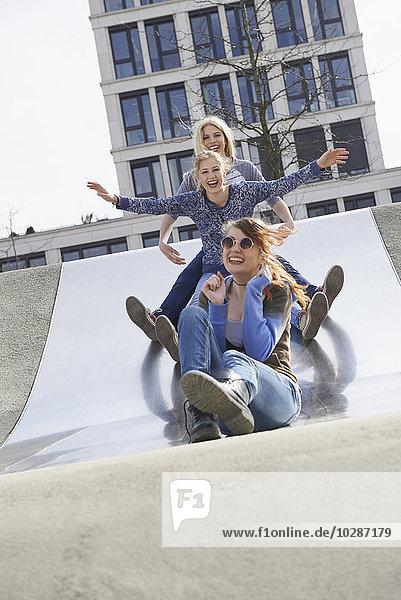 Three friends sliding down slide in a playground  Munich  Bavaria  Germany