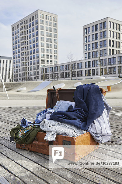 Open suitcase full of clothing on floorboard in playground  Munich  Bavaria  Germany