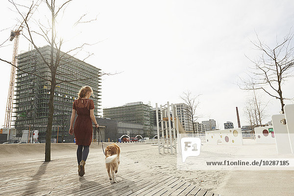 Rear view of a young woman walking in playground with dog  Munich  Bavaria  Germany