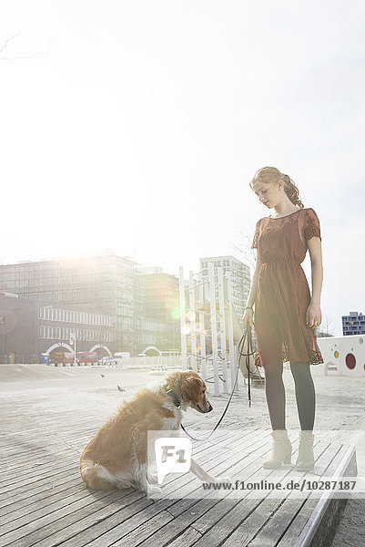Young woman standing in the playground with her dog  Munich  Bavaria  Germany