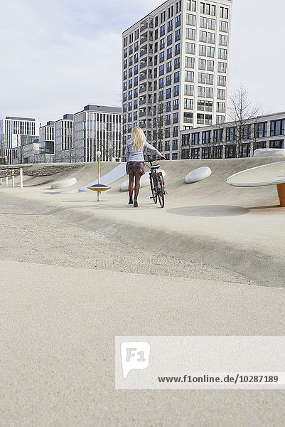Teenage girl walking with bicycle in a playground  Munich  Bavaria  Germany