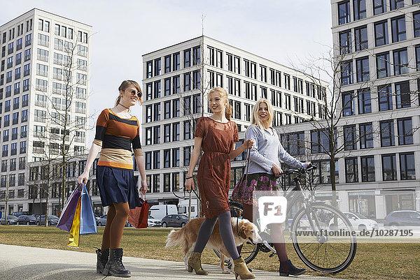 Three friends walking in a playground with dog  Munich  Bavaria  Germany