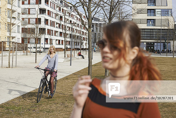 Teenage girl riding bicycle and young woman with cigarette in foreground  Munich  Bavaria  Germany