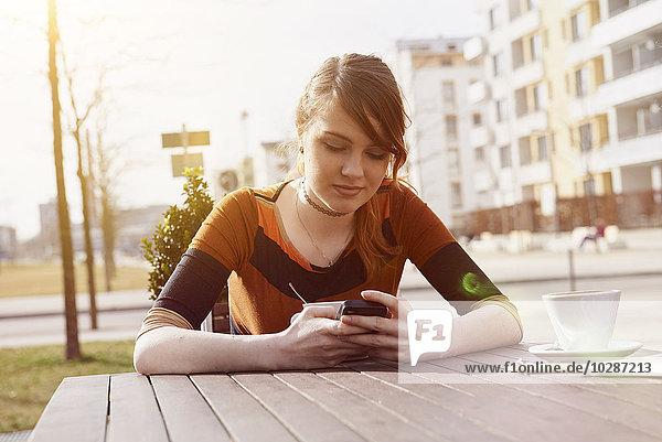 Young woman text messaging at sidewalk cafe  Munich  Bavaria  Germany Young woman text messaging at sidewalk cafe, Munich, Bavaria, Germany