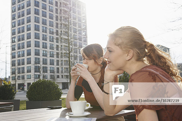 Young woman having coffee with her friend at sidewalk cafe  Munich  Bavaria  Germany