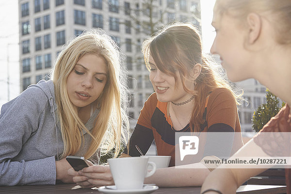 Three friends text messaging at sidewalk cafe  Munich  Bavaria  Germany