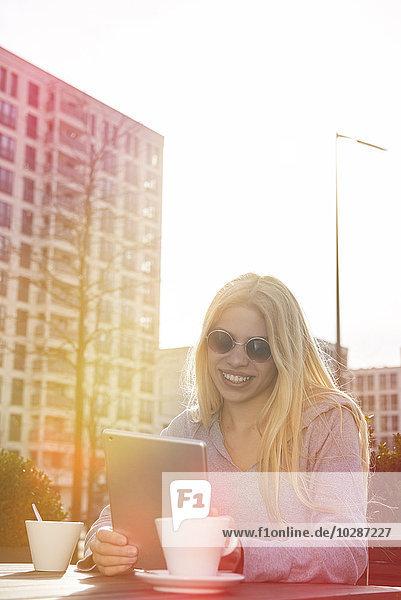 Teenage girl using a digital tablet at sidewalk cafe  Munich  Bavaria  Germany