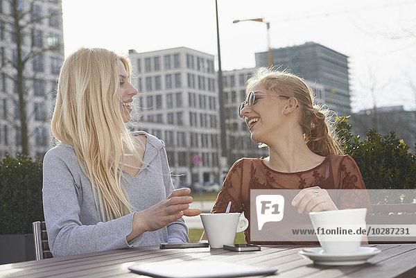 Two friends having fun at sidewalk cafe  Munich  Bavaria  Germany