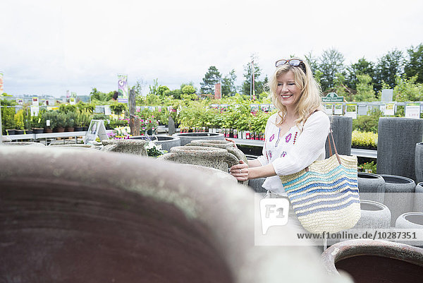 Mature woman choosing urn in greenhouse  Augsburg  Bavaria  Germany