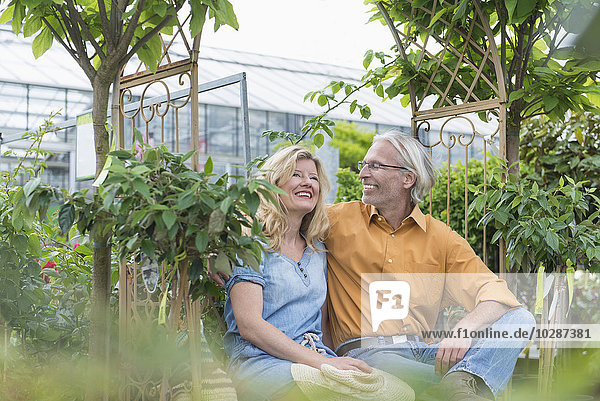 Mature couple sitting on a bench and smiling in plant nursery  Augsburg  Bavaria  Germany