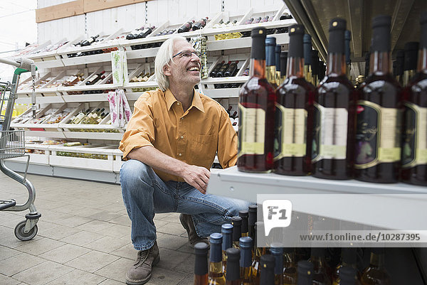 Customer looking wine bottles in supermarket and smiling   Augsburg  Bavaria  Germany