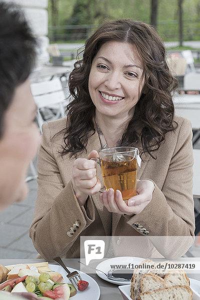 Two friends talking and having tea in sidewalk cafe  Bavaria  Germany
