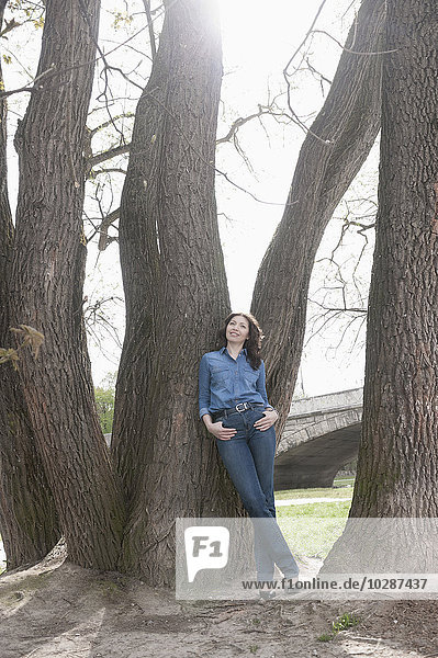Mature woman leaning against tree in park  Bavaria  Germany
