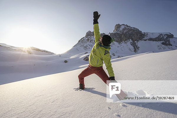 Man doing yoga on snowcapped mountain during sunrise  Tyrol  Austria Man doing yoga on snowcapped mountain during sunrise, Tyrol, Austria