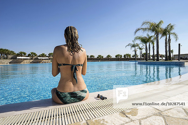 Rear view of mature woman sitting at poolside  Puglia  Italy