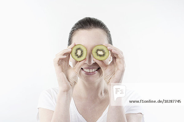 Mature woman holding kiwi slices in front of her eyes  Bavaria  Germany
