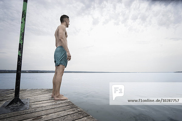 Mature man standing on pier and looking at view  Bavaria  Germany