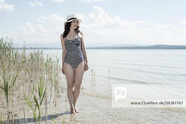 Mature woman walking in swimsuit at lake  Bavaria  Germany