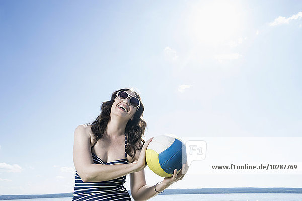Mature woman playing volleyball on the beach  Bavaria  Germany Mature woman playing volleyball on the beach, Bavaria, Germany