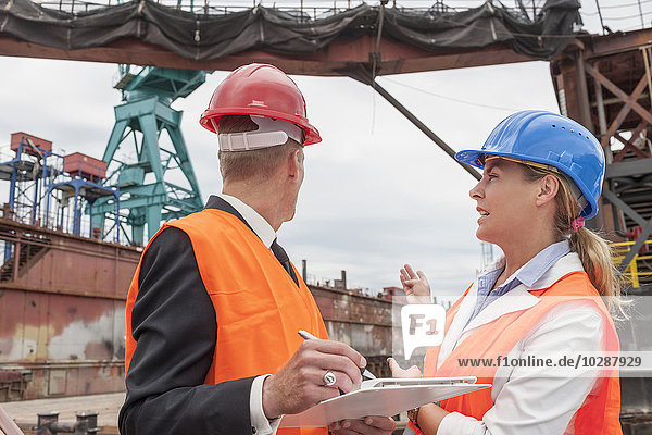 Dockers explaining to a manager during inspection of an industrial harbour  Hamburg  Germany