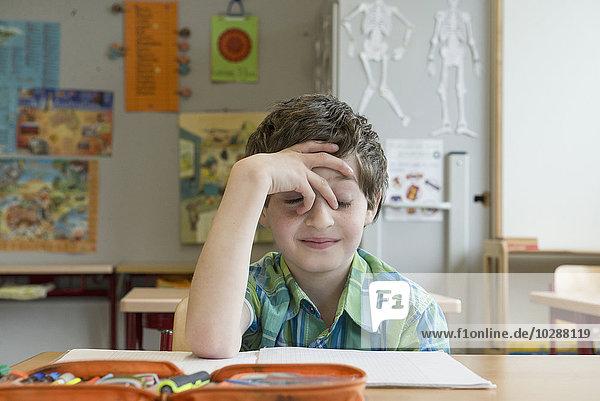 Bored schoolboy in classroom  Munich  Bavaria  Germany Bored schoolboy in classroom, Munich, Bavaria, Germany