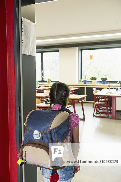 Rear view of a schoolgirl entering in classroom  Munich  Bavaria  Germany