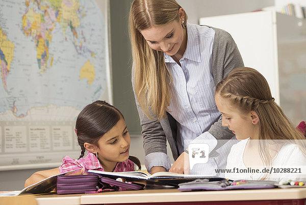 Female teacher helping students in classroom  Munich  Bavaria  Germany