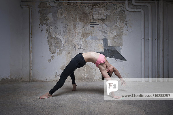 Mid adult woman practicing wild thing pose in yoga studio  Munich  Bavaria  Germany
