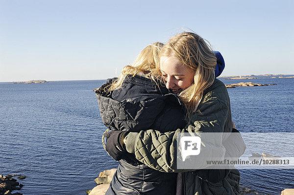Schweden  Bohuslan  Lysekil  Junge Frauen beim Umarmen am Strand