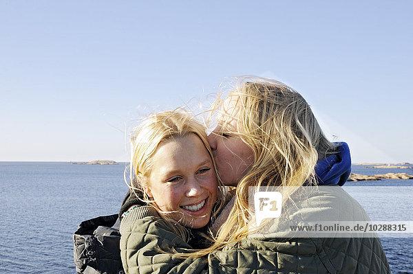 Sweden  Bohuslan  Lysekil  Young woman kissing her friend on cheek
