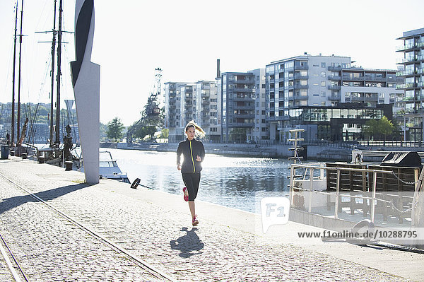 Sweden  Sodermalm  Norra Hammarbyhamnen  Hammarby Sjostad  Young woman jogging by waterfront