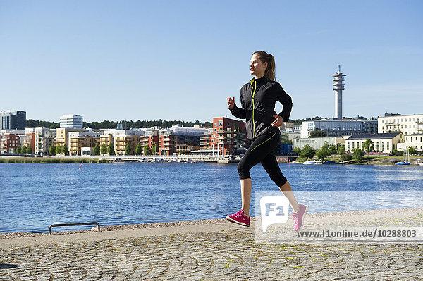 Schweden  Sodermalm  Norra Hammarbyhamnen  Hammarby Sjostad  Junge Frau beim Joggen am Wasser