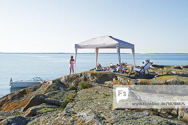 Schweden  Sodermanland  Stockholm Archipel  Varmdo  Norsten  Reife Paare entspannen sich am felsigen Strand