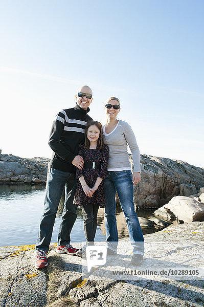 Schweden  Bohuslan  Smogen  Porträt eines Mädchens (8-9) mit Eltern am Felsenstrand