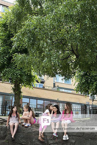 Schweden  Vastra Gotland  Fünf Schülerinnen (10-11) sitzen auf Felsen vor der Schule