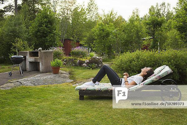Sweden  Ostergotland  Girl (12-13) relaxing in garden